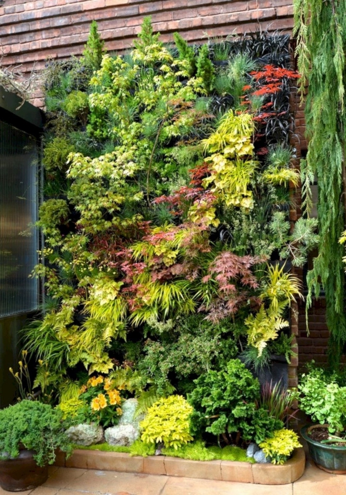 un coin de verdure rassérénante aménagé dans le jardin avec un mur végétal composé de plantes de couleur et de taille variée
