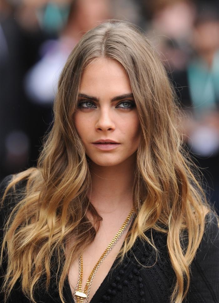 exemple de balayage sur cheveux chatain, maquillage pour yeux clairs à effet smoky, modèle de robe noire avec décolleté en V