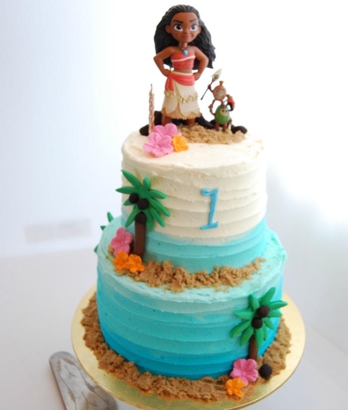 exemple de deco vaiana sur un gâteau à design océan en bleu et blanc avec figurines des personnages de Disney