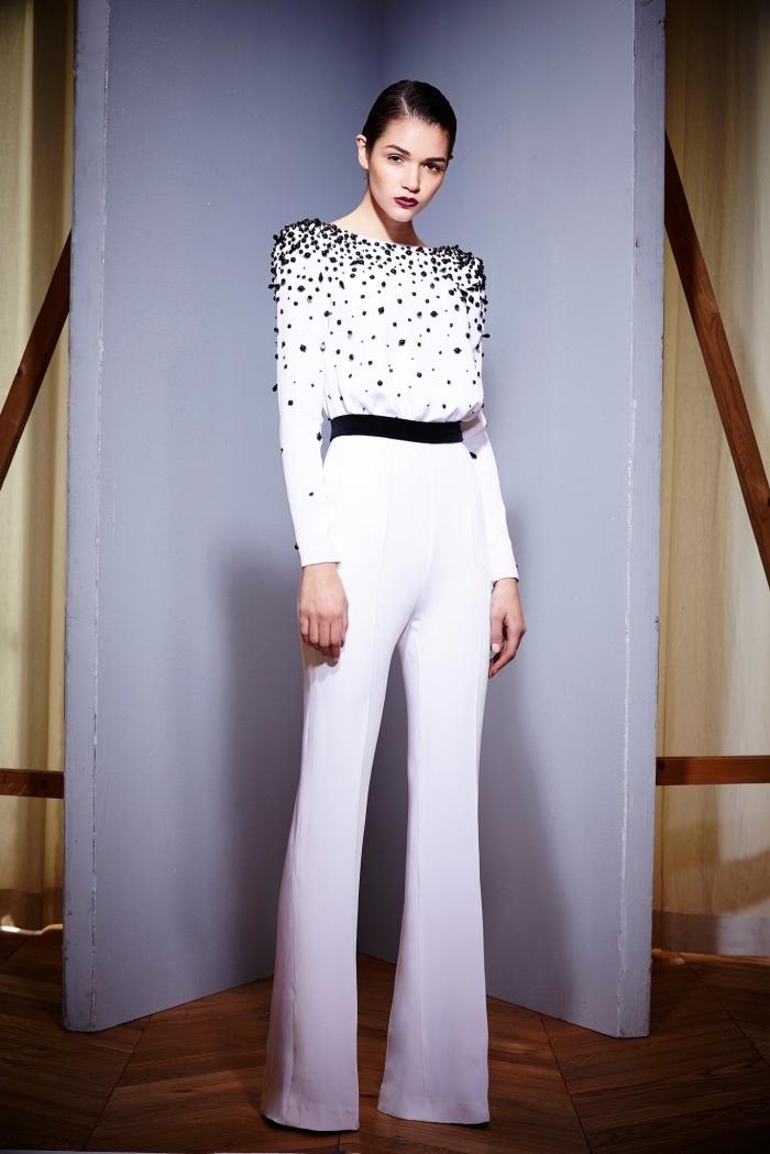 tenue officielle femme en combinaison chic aux manches longues en blanc avec décoration noire sur le top et ceinture