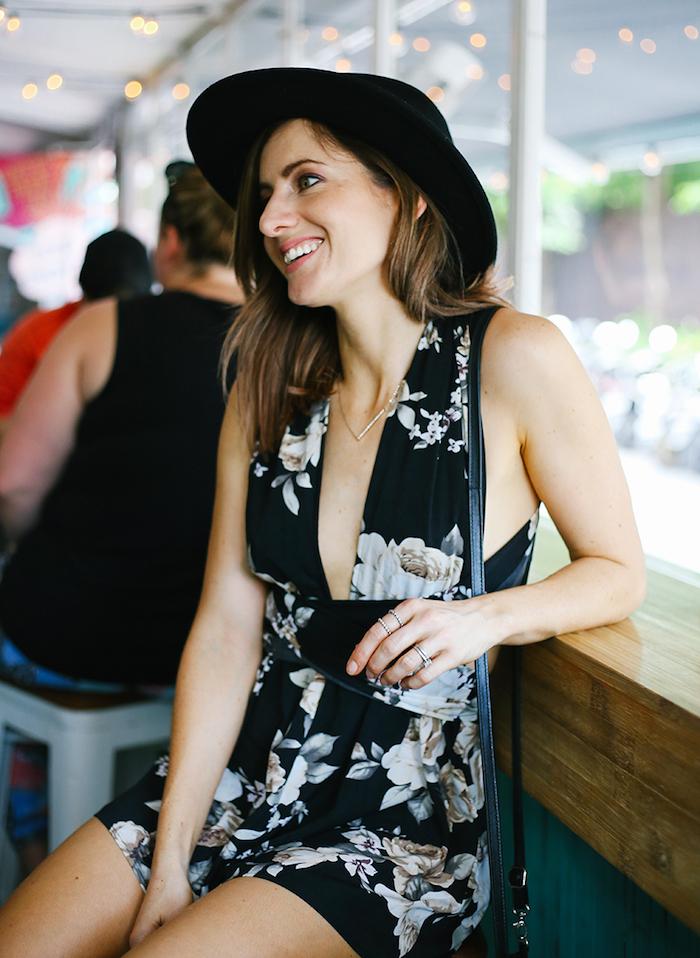 Belle femme souriante en combishort dos nu, combinaison pantalon court femme, originale tenue de soirée fleurie noir