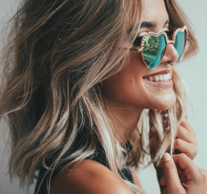 cheveux volumineux texturisés avec dea boucles façon beach waves sur cheveux en carré long ondulé flou, lunette de soleil femme forme de coeur