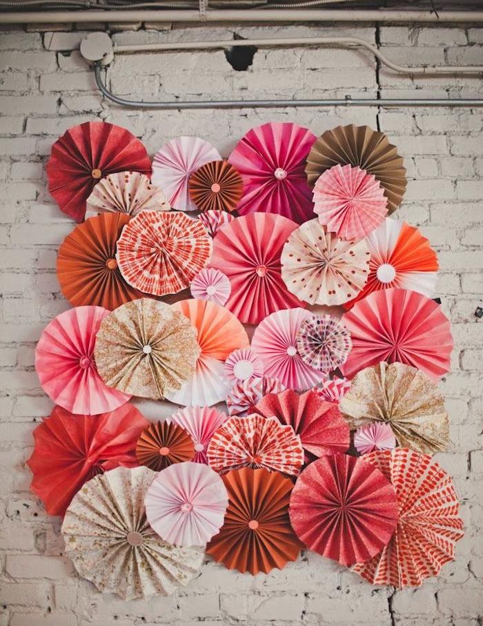exemple de decoration murale sur mur de briques blanches décorée d éventails en papier rose, rouge, blanc, orange