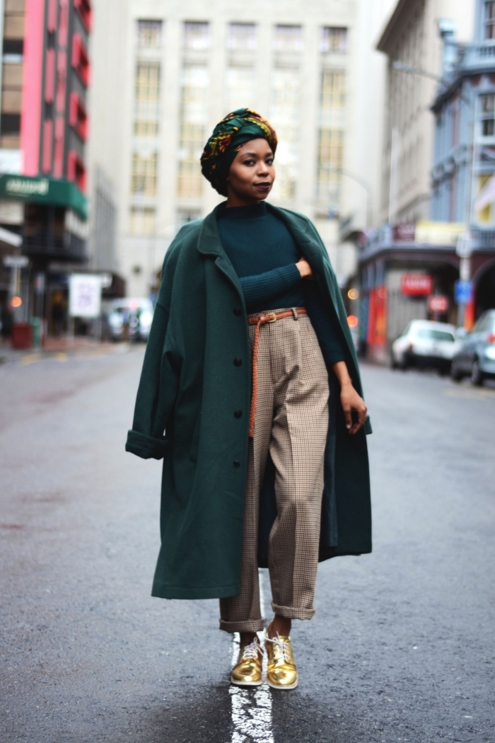 comment porter le turban en wax tissu africain avec une tenue urbaine chic, look chic et décontarctée en pantalon tailleur, pull vert et manteau oversize vert