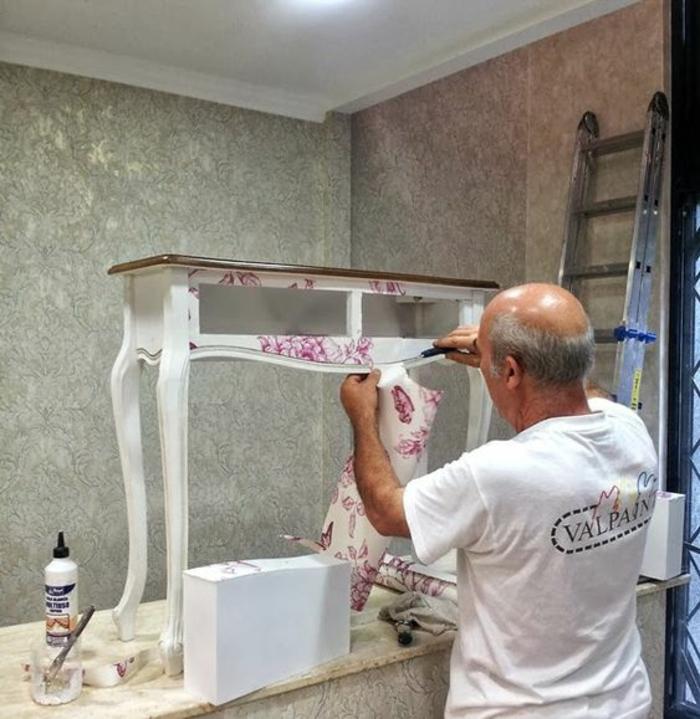 meuble relooké, table en bois peinte en blanc et recouverte de papier peint en blanc et rouge, meuble avec des pieds recourbés, homme qui travaille sur le relooking de la vieille table