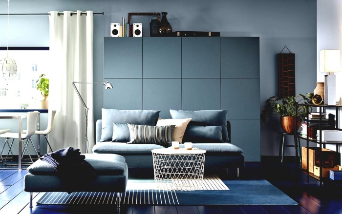 un canapé bleu canard assortie avec le meuble de rangement besta de même couleur bleu vert, ambiance sereine et apaisante dans un salon bleu vert aux accents blancs