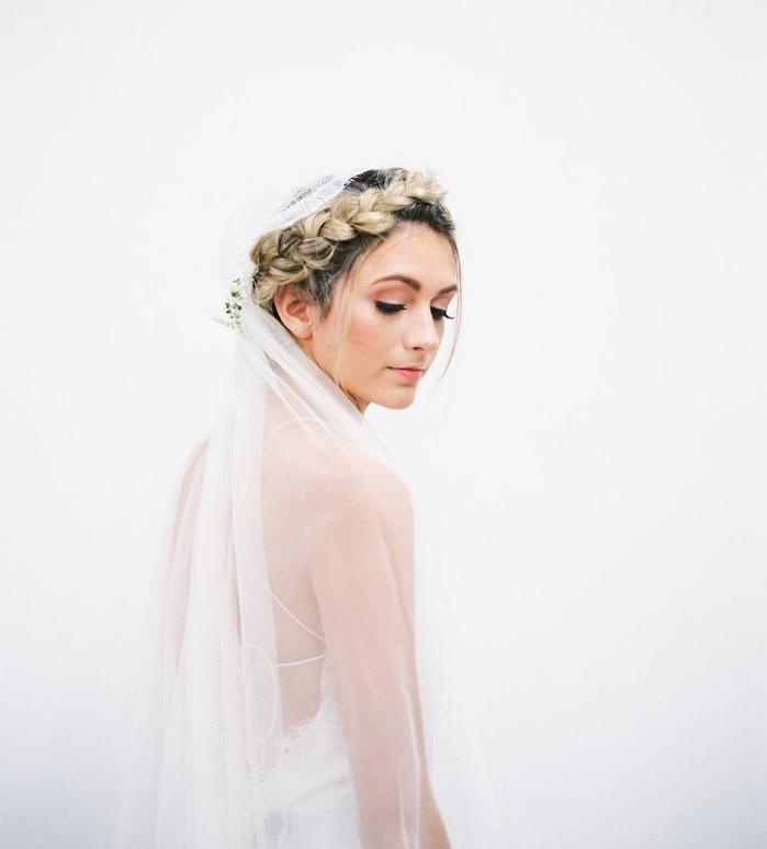 coiffure tresse couronne traditionnelle avec de petites mèches encadrant le visage, voile blanche, robe de mariée simple