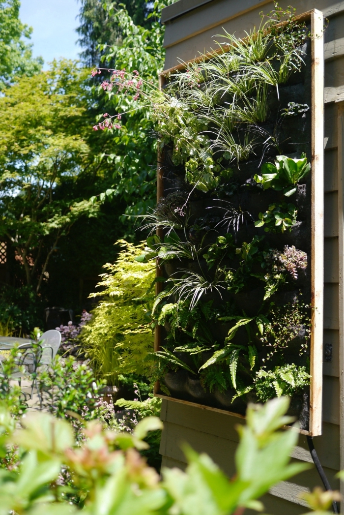 système de mur vegetal exterieur avec une structure en bois, des poches de feutre horticole et un système d'arrosage automatique