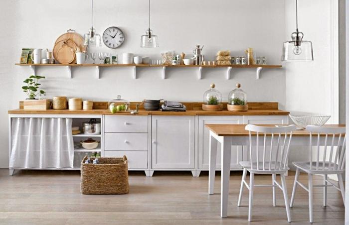 cuisine en style shabby chic en bois peint en blanc et en bois naturel couleur claire, horloge ronde au-dessus d'une étagère en bois clair, plan en bois clair pour le meuble du lavabo, parquet en nuances grises