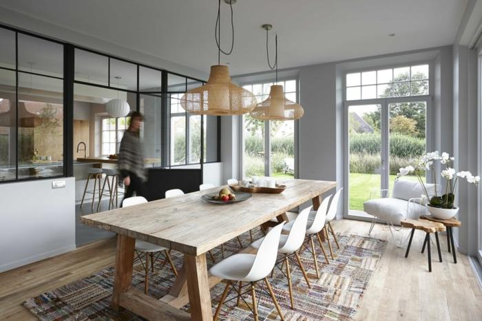 cuisine semi ouverte avec une cloison verriere, tapis patchwork rectangulaire, grande table à manger, lampes suspendues, maison plain pied