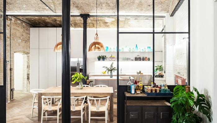 cuisine et salle à manger style industriel, deux lampes cuivrées suspendues, un mur blanc avec mur briques et plafond en béton