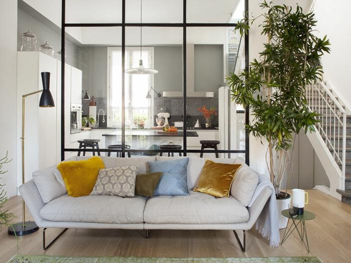 cloison verriere, sofa gris pâle, lampe de sol noire, escalier blanc, tabourets noirs, cuisine gris et blanc