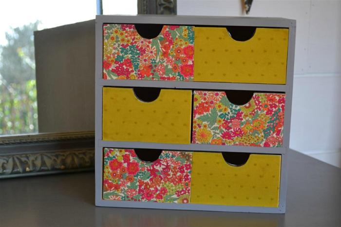meuble relooké aux tiroirs de rangement six casiers aux portes couvertes de papiers peints en couleurs vives, motifs petits pois et motifs fleuris