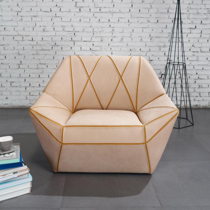 un meuble en bois habillé de simili cuir couleur caramel clair, motifs figures géométriques triangulaires, mur en briques blanches