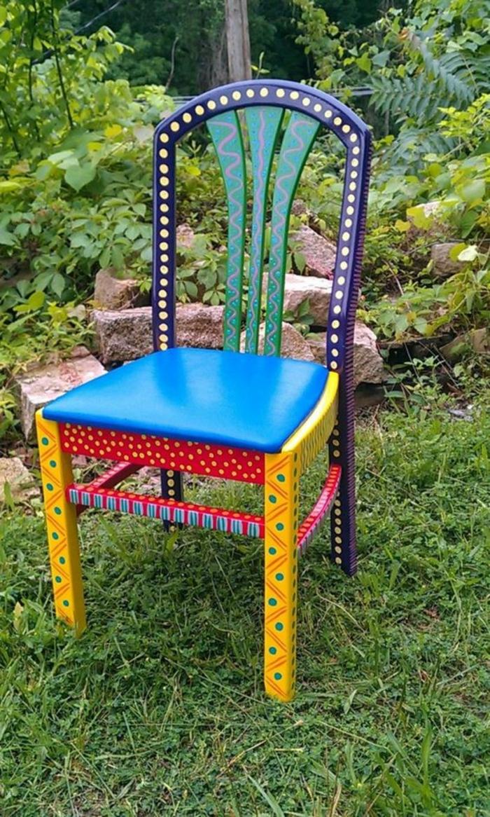 un meuble en bois haut en couleurs et en motifs, sans accoudoirs, dossier noir avec des pois blancs, pieds jaunes avec des pois verts