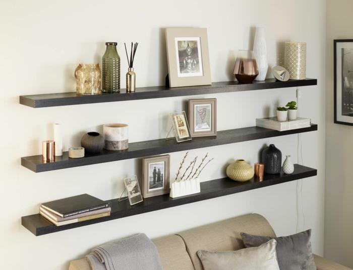 comment repeindre un meuble sans le poncer, étagères en bois peintes en noir, murs blancs, tableau au cadre fin en bois noir, canapé en tissu vert olive