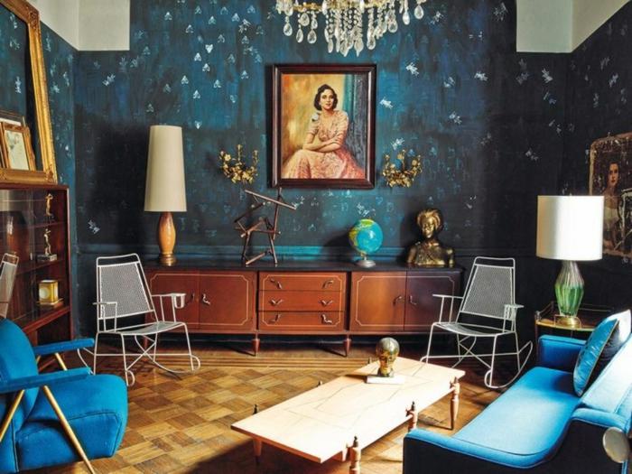 petit séjour artistique, canapé et fauteuil bleu style mid century, buffet bas, lampadaires vintage, plafonnier pampilles