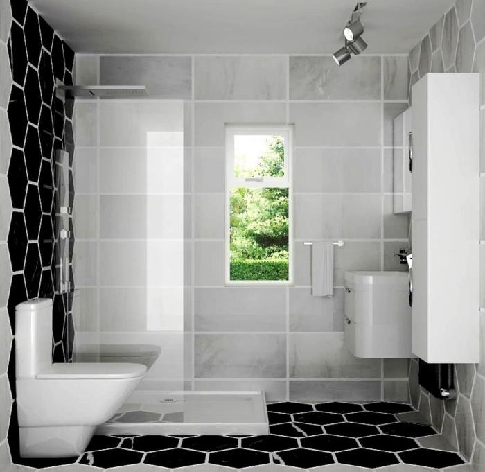 design intérieur moderne en blanc et noir dans une petite salle de bain avec cabine à douche italienne au carrelage gris clair et noir