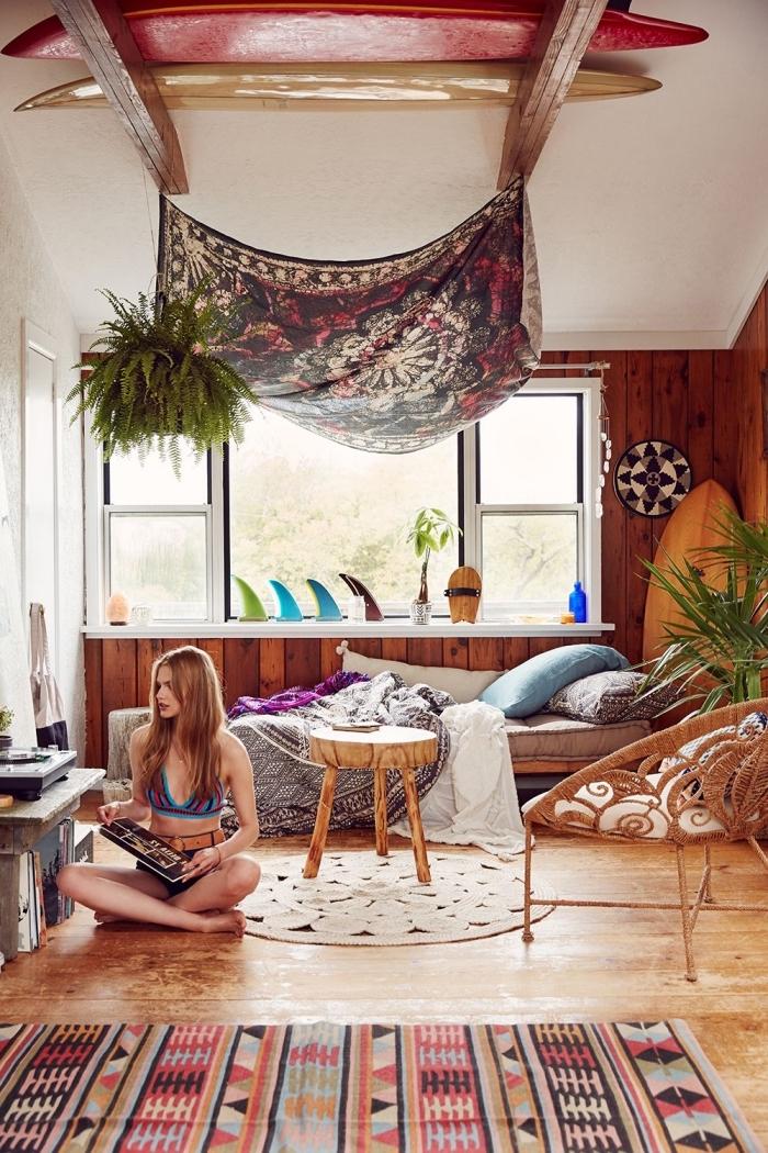 ambiance bohème chic dans une pièce aux murs blanc avec revêtement partiel de bois foncé, modèle de tapis bohème aux motifs géométriques