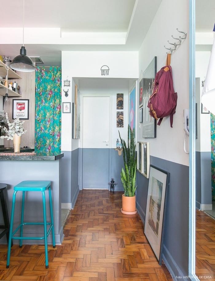 une bande de couleur bleu gris sur le bas des murs qui se prolonge sur la porte, une porte de chambre graphique
