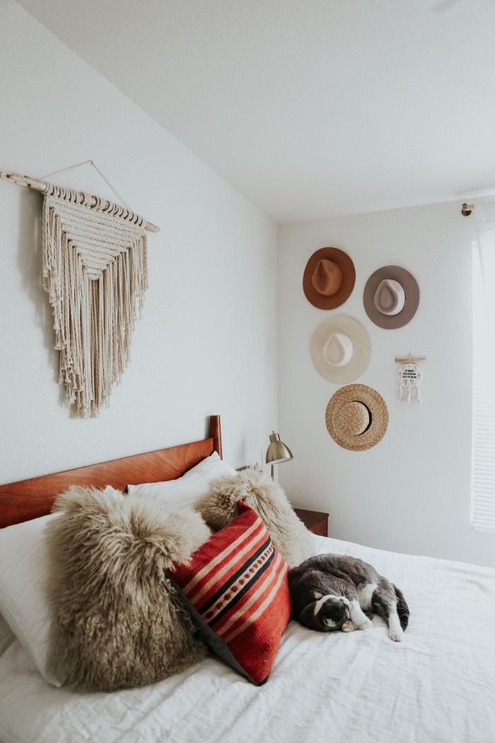 modèle de design intérieur style bohème dans une pièce blanche avec large lit en tête de lit en bois foncé et diy macramé