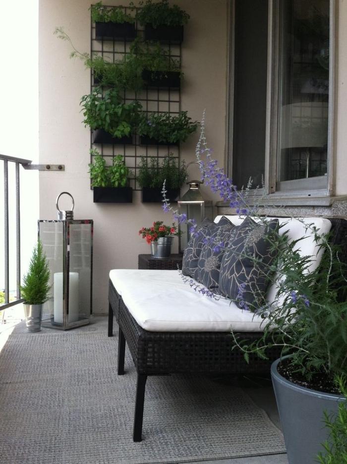 idée pour créer un jardin vertical dans un petit balcon, des pots noirs fixés sur une grille métallique