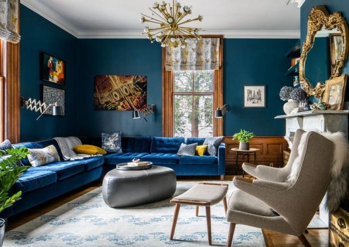 la tendance ton sur ton adopté dans un salon élégant avec l'association d'un canapé bleu marine en velours et les murs couleur bleu pétrole