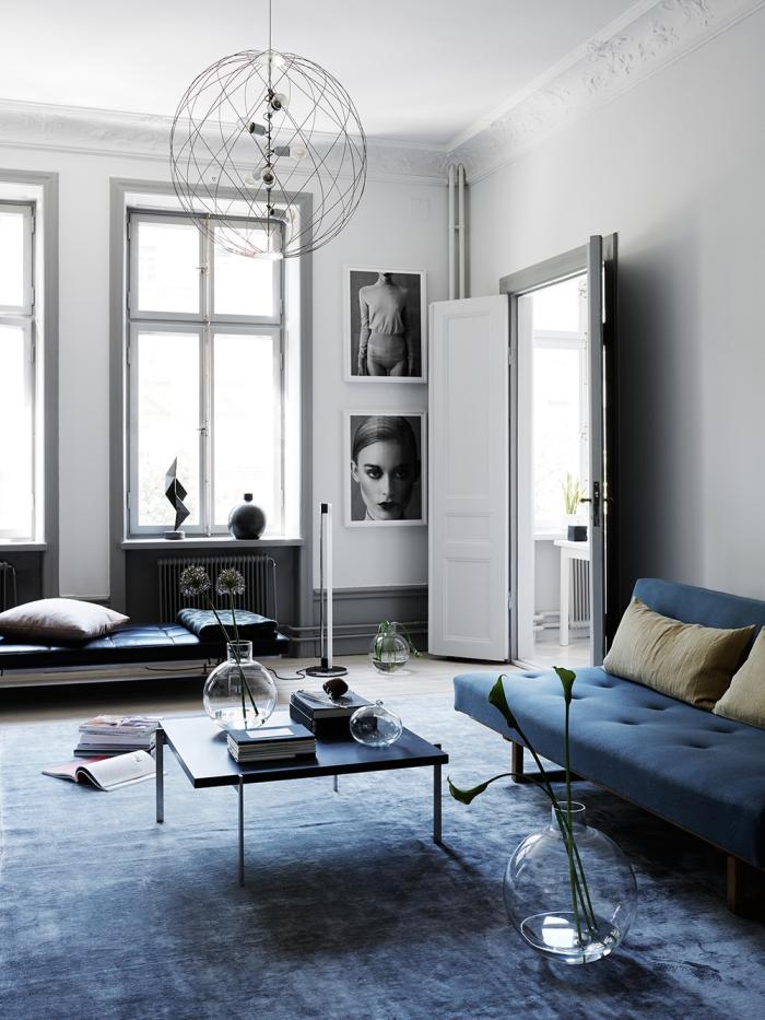 déco salon style minimaliste en bleu, blanc et gris avec des meubles aux lignes épurées, un canapé bleu marine de même couleur que le tapis