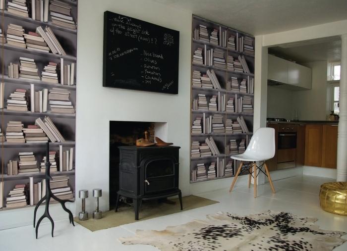 deux lés de papier peint trompe l'oeil imitation bibliothèque posés des deux côtés de la cheminée en fonte vintage