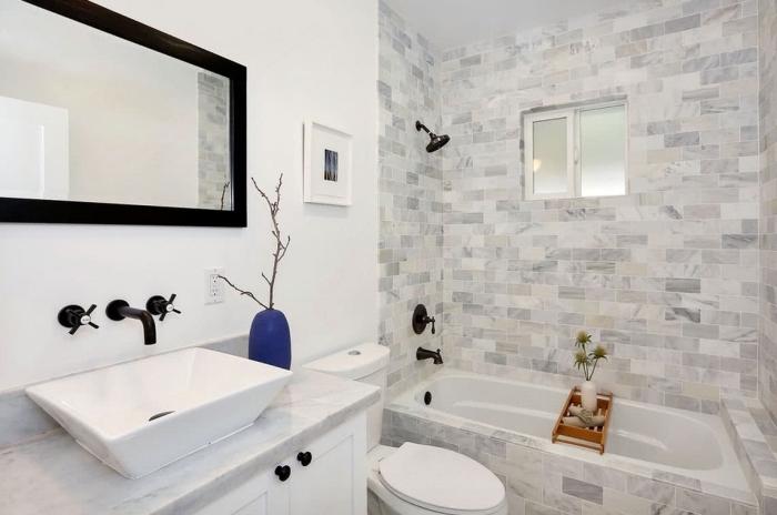 idée comment aménager une petite salle de bain blanche au carrelage baignoire gris et blanc avec miroir et robinets en noir