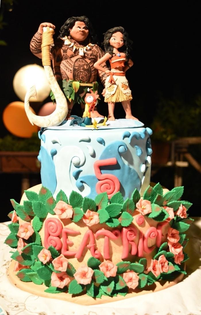 gateau anniversaire vaiana à deux étages avec fondant coloré en bleu clair et bleu foncé, modèle de petites fleurs en orange avec feuilles vertes en pâte sucre