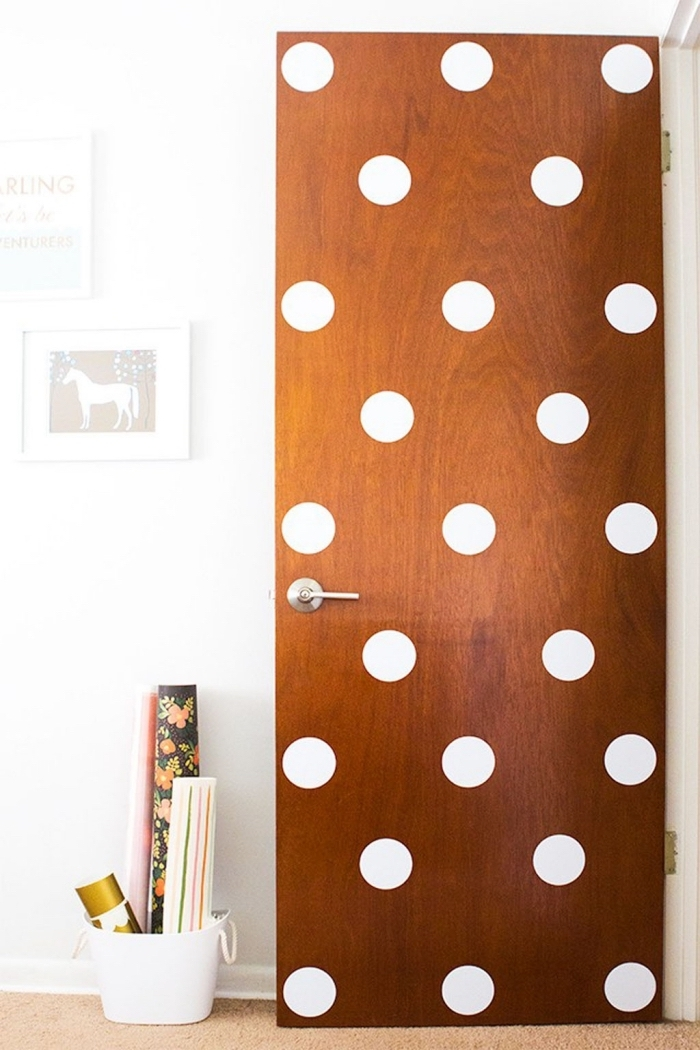 déco de porte originale et gaie de pois blancs, en contraste avec l'aspect vintage du bois, des stickers pour porte originaux pour transformer une porte plance en bois