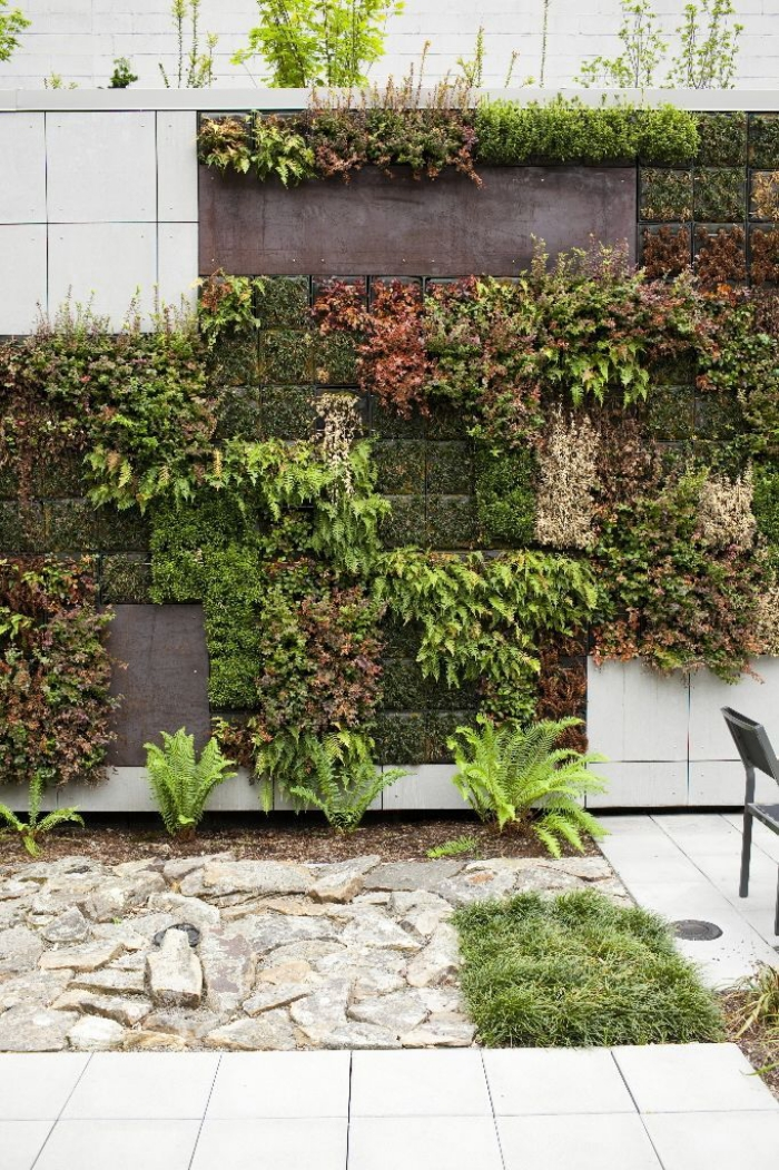 idée déco murale originale pour le patio ou le jardin, un mur vegetal exterieur en sphaigne du chili, avec des plantes de couleur et de texture différente