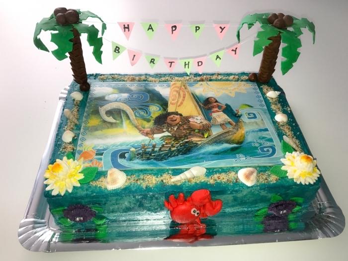 exemple de decoration anniversaire fille avec un gâteau fait maison sur le thème Disney avec les personnages Vaiana et Maui
