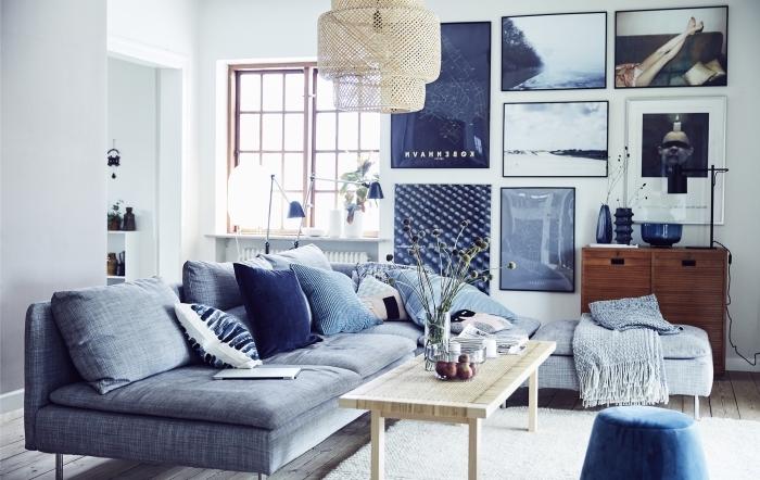 la présence d'un luminaire en rotin et d'une table basse en bois clair rend le salon gris et bleu plus convivial et accueillant , un canapé bleu marine nuance indigo accessoirisés avec des coussins en camaïeu de bleu