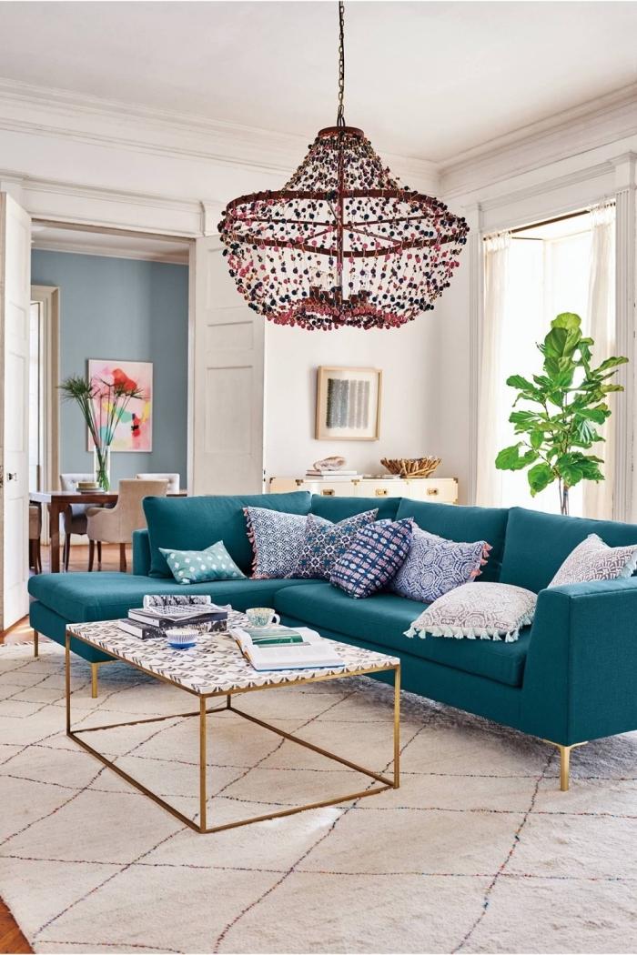 comment adopter la deco bleu canard dans un salon, canapé d'angle couleur bleu vert qui devient la pièce centrale dans un salon blanc de style bohème chic