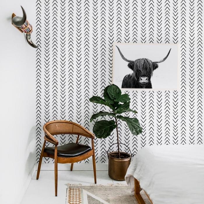 pièce aménagée en style bohème chic avec décoration murale blanc et noir et meubles de bois, modèle de tapis bohème beige et blanc