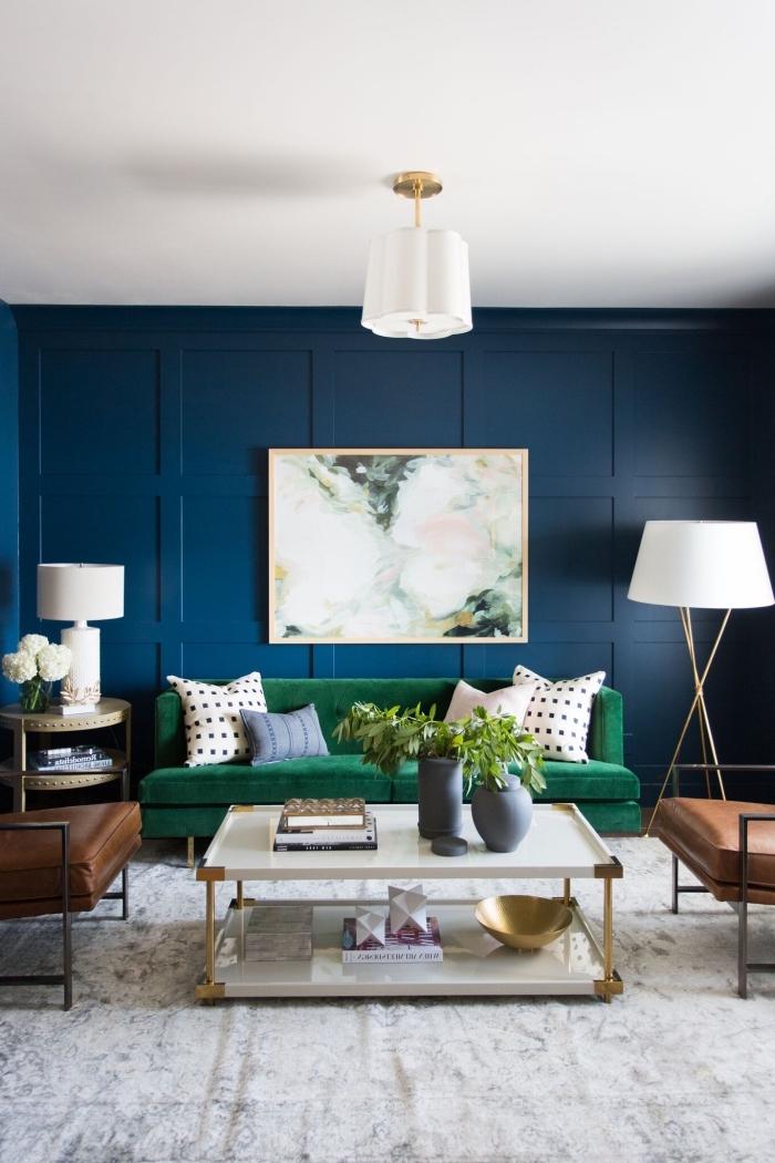 le fond bleu foncé, sublimé par un tableau effet marbre et le canapé vert, apporte de la profondeur au petit salon