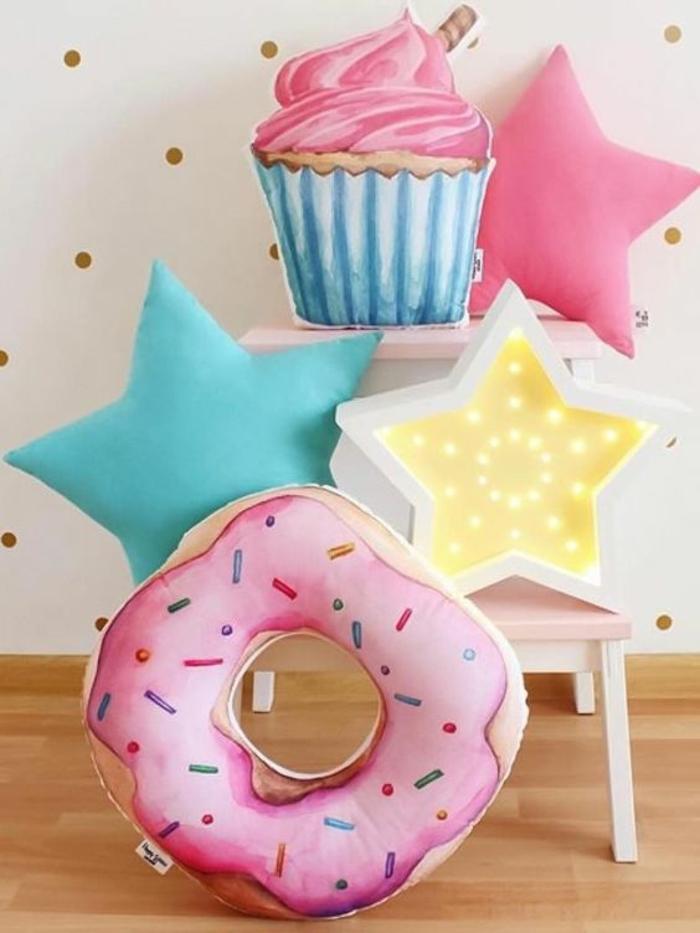des coussins taille grande en forme d'étoiles, donuts et cup cakes, parquet nuances beiges, mur en blanc aux pois dorés, cinq coussins aux formes attractives en couleur rose pale et vieux rose