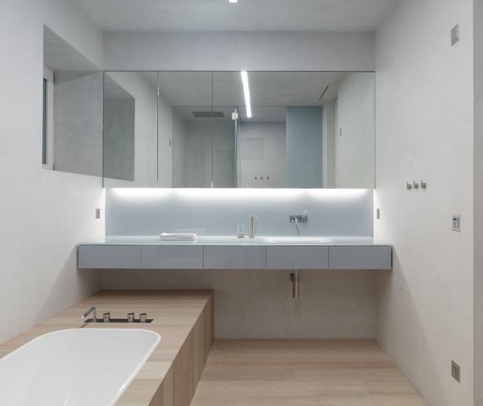 petite salle de bain avec baignoire et revêtement de sol à design bois aux murs blancs avec large miroir et éclairage sous meuble