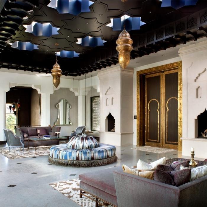 salon de style ethnique et exotique aux murs hauts avec finitions en bois, pièce au plafond noir et verre avec plancher gris clair