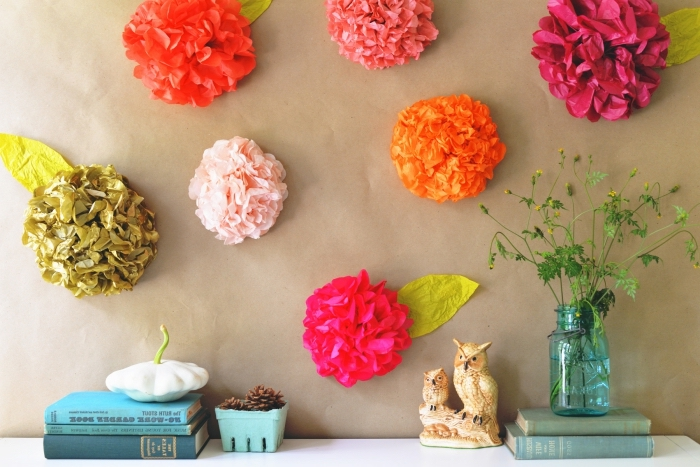 exemple de décoration murale en fleurs fait maison en papier crépon de couleurs orange et rouge, activité manuelle ado ou adulte facile