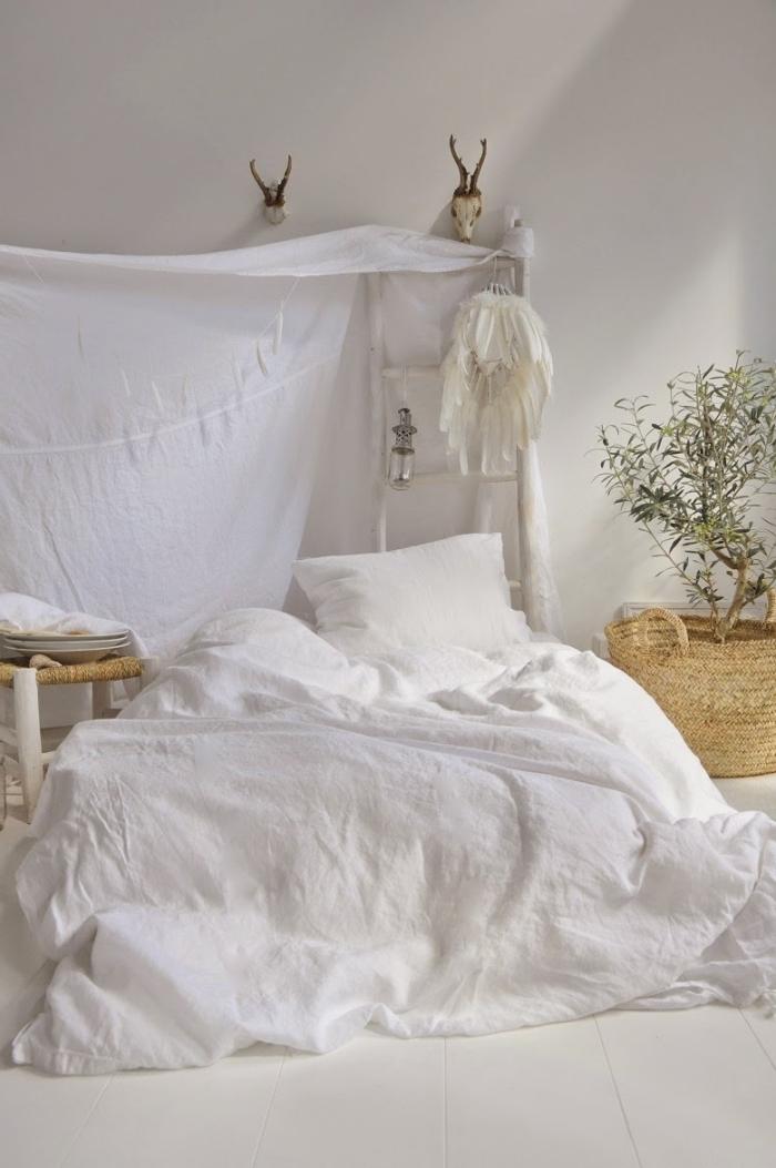 décoration de lit au sol à imitation lit baldaquin avec un drap blanc et échelle de bois peint blanc avec attrape rêve en plumes blanches