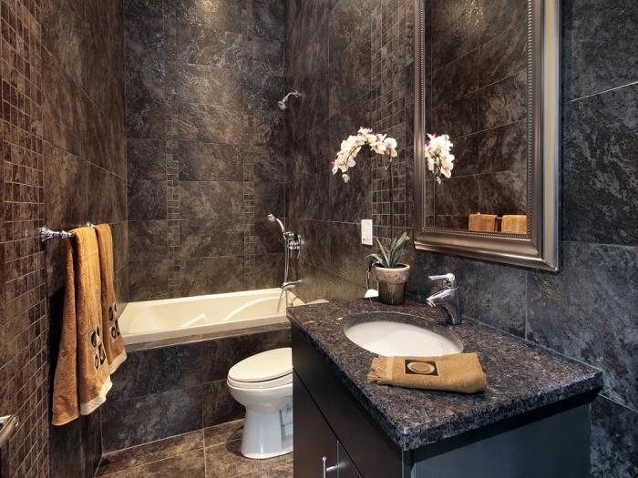 déco petite salle de bain foncée au carrelage marron avec baignoire et cuvette wc en blanc, meuble sous vasque noir