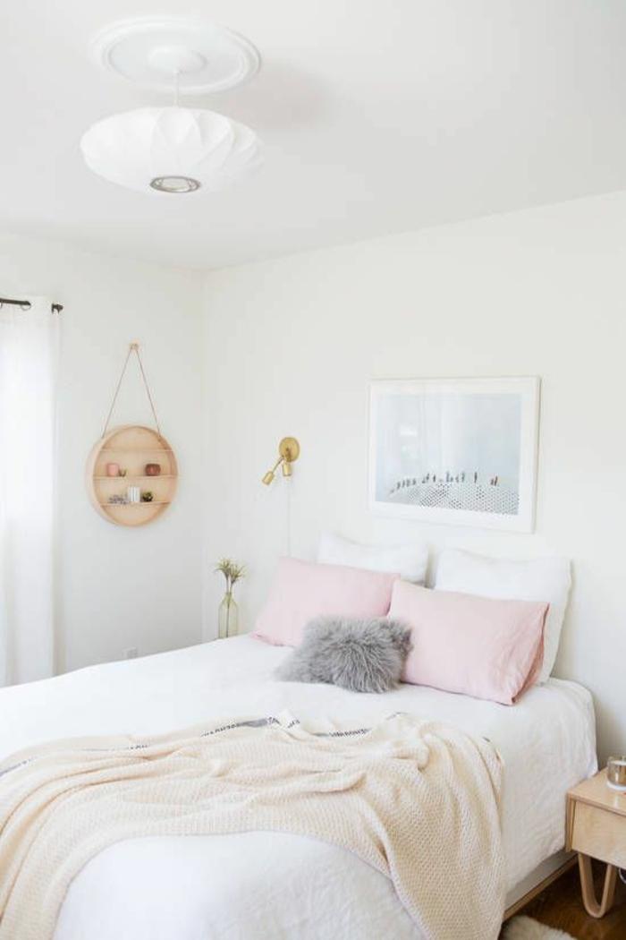 chambre d'adulte, deux grands coussins en couleur rose poudré, plafond blanc avec plafonnier en verre mat blanc, tableau avec paysage marin au cadre blanc au-dessus du lit