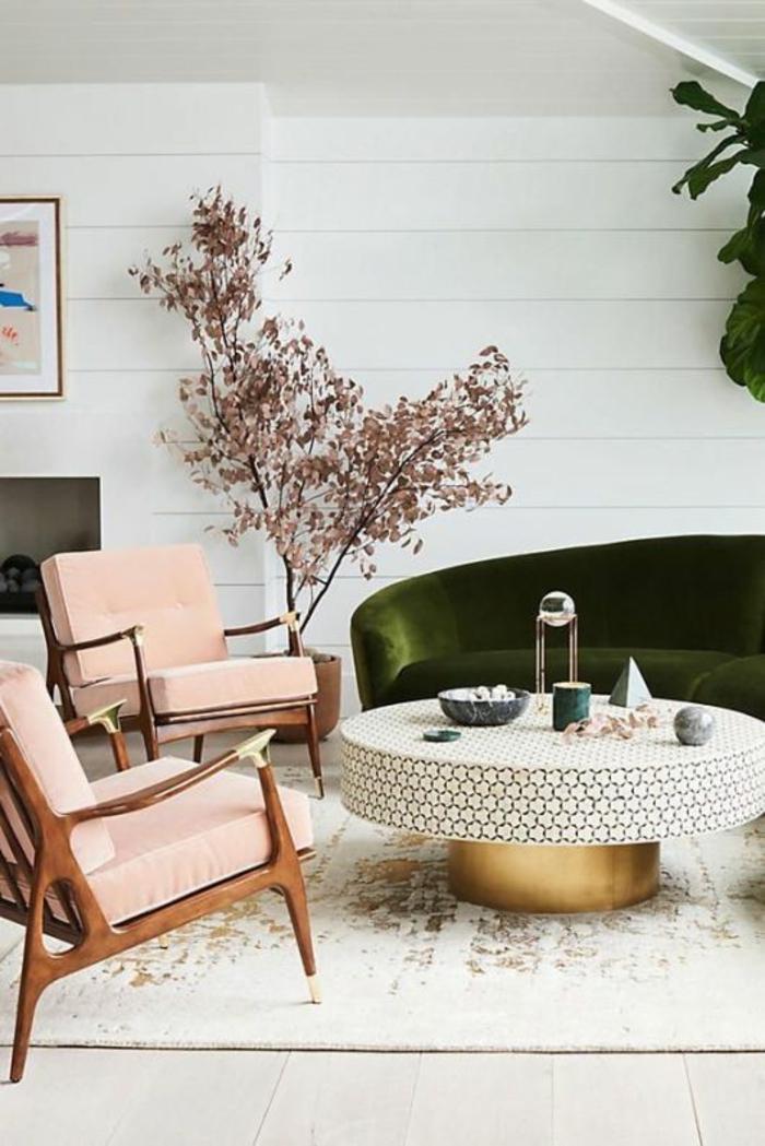 chambre rose poudré et taupe, murs blancs, deux fauteuils en couleur rose pale en style rétro, petit arbrisseau aux feuilles roses, parquet clair avec tapis en blanc et doré, table ronde avec base cylindrique dorée, plan rond en blanc aux motifs ruches dorées