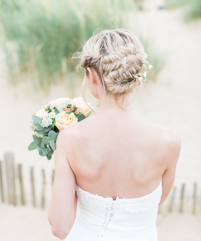 idée de coiffure tresse mariage avec des tresses en épi de blé ramenées en arrière sous la forme de chignon, robe de mariée blanche