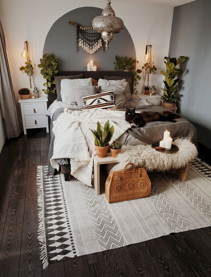 exemple de deco chambre boheme avec objets ethniques, pièce aux murs blancs avec déco pan de mur en gris et parquet foncé