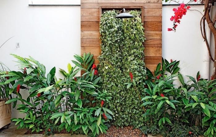 un coin de fraîcheur d'été aménagé dans le jardin avec une douche extérieur et un mur végétalisé aménagé derrière