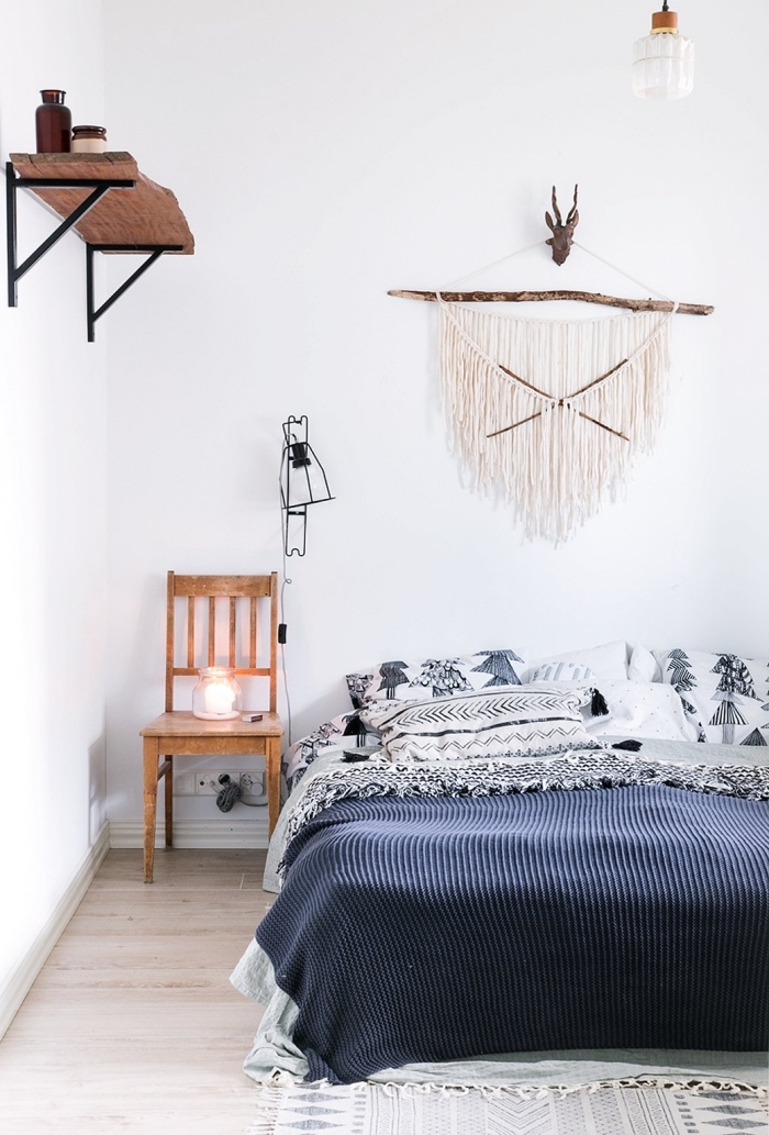 exemple de chambre boheme chic aux murs blancs avec plancher de bois clair et étagère murale en bois massif, modèle de lit couvert de coussins et de plaid boho chic